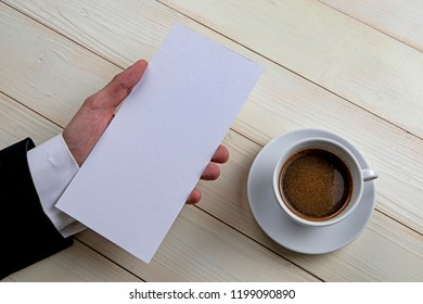 Mens hand holding empty white flyer on wooden background