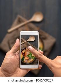 Men's hand holding smartphone capturing thai food. Tomyum