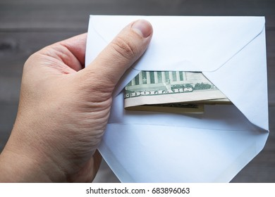 men's hand holding an white mailing envelope with US dollars in cash