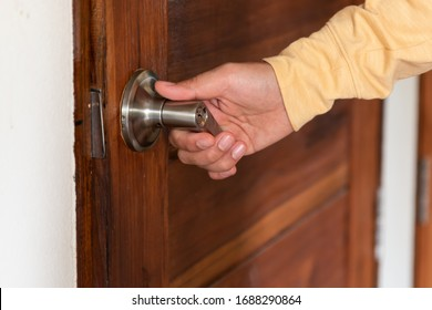 Men's hand opens wooden door home. Close up.