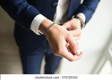 Men's hand in a suit, a silver bracelet on the man's hand, the hand of a businessman, businessman in a suit, hands of a man close-up, man puts on a silver bracelet, hands of a man in the blue suit