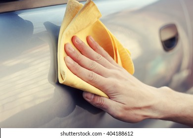 Men's hand with yellow cloth cleaning car. Photo with toning