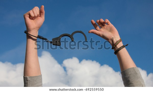 Men's hands against the sky in handcuffs