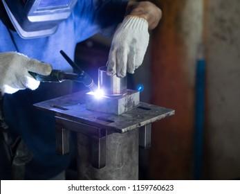 Men's hands with argon welding machine.  repair pipe stainless argon welding industrial construction