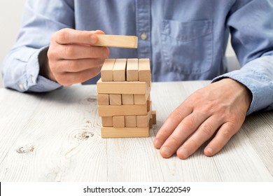 Men's hands in a blue office shirt are folding a pyramid of wooden bars, which can be inscribed. Fragment. Unrecognizable person. Against the background of a beige table with a wooden texture.