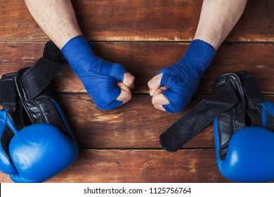 Men's hands in boxing bandages and boxing gloves on a wooden background. Concept preparation for boxing training or combat. Flat lay, top view.