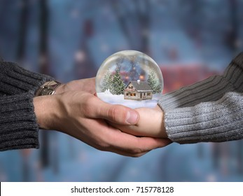 Men's hands and child's hands holding a glass ball. Ball Christmas scenery inside. Fairy house, snow, winter.