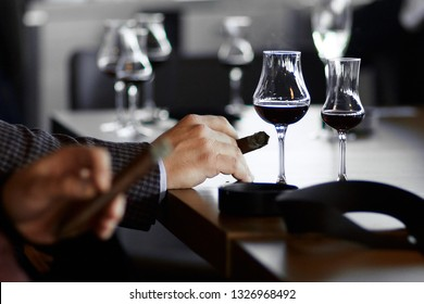 men's hands with a cigar and  glasses of mulled wine and champagne on the table