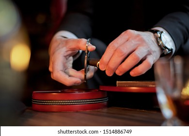 Men's hands cut a cigar with scissors. On the table lies a cigar, a lighter, a clock.