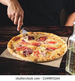 Men's hands cut the pizza into pieces