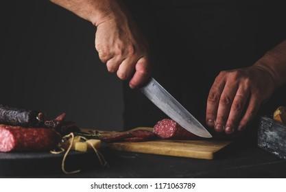 Men's hands cut sausage salami on a cutting board