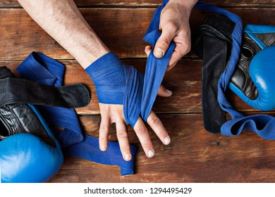 Men's hands during taping before a boxing match against a wooden background. The concept of training for boxing training or fighting. Flat lay, top view