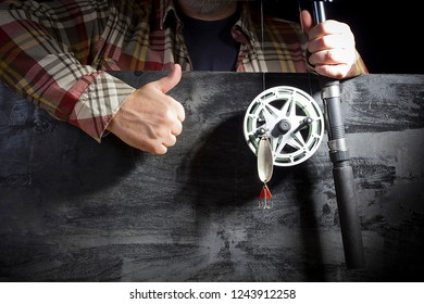 Men's hands with fishing tackle on the background of the board
