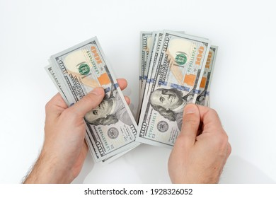 Men's hands hold and count hundred dollar bills on white background. Successful man considers salary. Close up photo