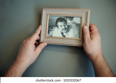 Men's hands hold a wooden frame with a black and white photo. Sentimentality on father's day.