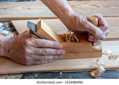 Men's hands hold a wooden jointer close-up. Light wood boards, shavings, sawdust