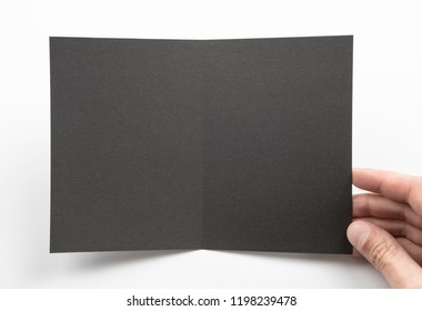 Mens hands holding empty black booklet on white background. View from above