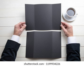 Mens hands holding empty black booklet on gray background. View from above