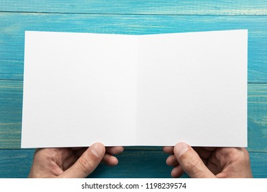 Mens hands holding empty white booklet on blue wooden background. View from above