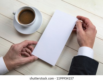Mens hands holding empty white flyer on wooden background