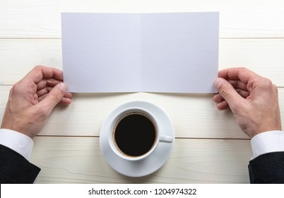 Mens hands holding empty white booklet on wooden background. View from above