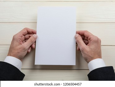 Mens hands holding empty white letterhead on wooden background. Blank paper mock-up
