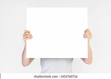 men's hands holding empty white poster, copy space
