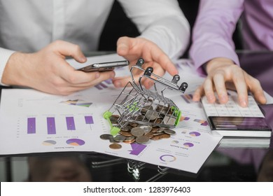 Men's hands holding phone and counting on calculator next to fallen Dummy shopping cart with scattered coins