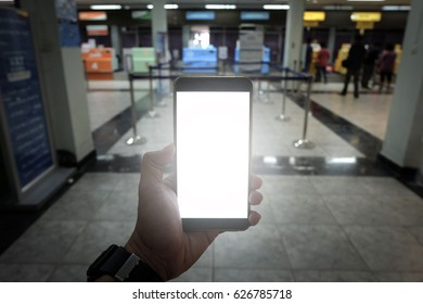 Men's hands are holding a smart phone for booking or check in on the abstract background of the airport blur.