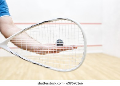 men's hands holding squash racket and ball. Racquetball equipment. Photo with selective focus