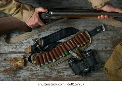 Men's hands with a hunting gun reload the cartridge.Male hunter in camouflage clothes ready to hunt with hunting rifle.
