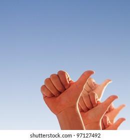 men's hands make thumbs up on blue sky