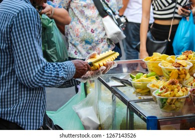 Men's hands are peeling pineapple peels.