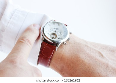 Men's hands, pointing the finger at the clock
