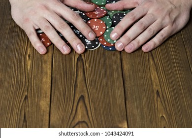 Men's hands and poker chips on a wooden background
