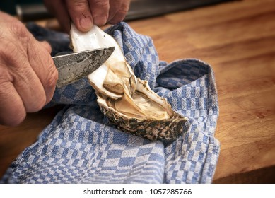 men's hands shucking a fresh oyster with a knife on a blue kitchen towel on a rustic wooden table, selected focus, narrow depth of field