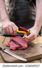 Men's hands and steaks of meat. Preparation of dinner man. Wooden table and old board. Beef and bitter colored pepper. Copy space.