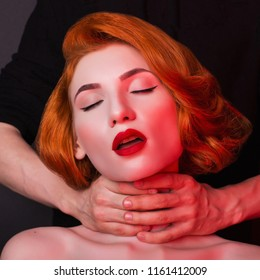 Men's hands stifle redhead girl on black background. Sexual bdsm doll. Model with open mouth and red sensual lips. Lady with hands on neck. Bdsm games. Photo in low key lighting. Maniac stifle victim
