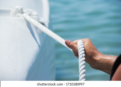 men's hands tied the rope on the yacht.