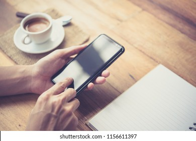 Men's hands are using a smartphone at home.