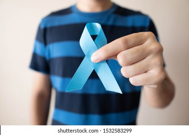 Men's health and Prostate cancer awareness campaign in November month. Close up of young man hands holding light blue ribbon awareness. Symbol for support men who living with cancer.