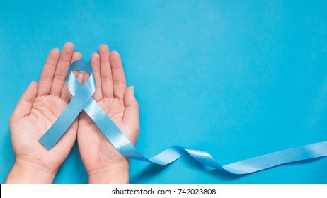 Men's health and Prostate cancer awareness campaign concept. Man hands holding light blue ribbon awareness w/ long tail on sky blue background. Symbol for support men who living w/ cancer. Copy space.