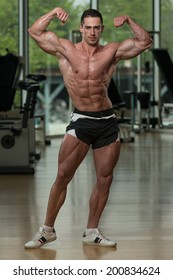 Men's Health - Serious Men Standing In The Gym And Flexing Muscles
