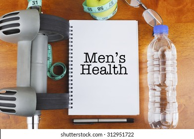 """Men's Health"" text on notebook with delicious green apple, measure tape, spectacle, a bottle of mineral water, and bodybuilding tools on wooden background - healthy, exercise and diet concept"