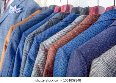 Chaquetas de hombres colgando en la tienda masculina. Fila de chaquetas para hombres colgando en el armario.