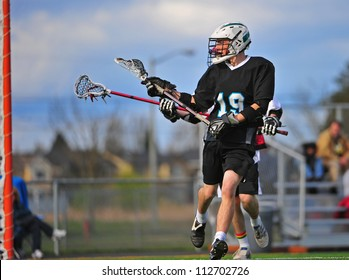 Mens lacrosse player taking a shot on the goal with the defender close behind him.