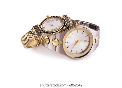 Mens and ladies gold and silver wrist watches on a white background.