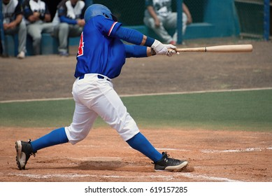 Men's league player in blue shirt swinging at a pitched ball