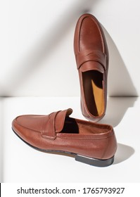 Men's leather brown loafers on a white background. Stylish men's shoes