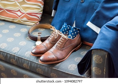 Men's leather new brown shoes closeup still life on blue couch with socks, watch, suit for getting ready wedding or interview preparation in room